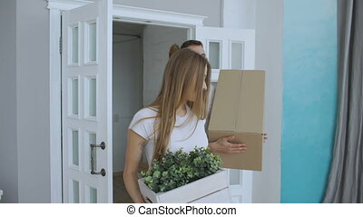 Young happy couple first time walking in new house after moving and kiss each other