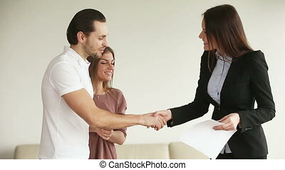 Young happy couple getting keys from new house