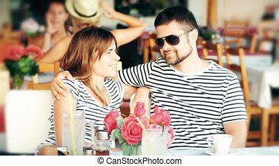 Young happy couple having coffee in a street cafe on their vacation