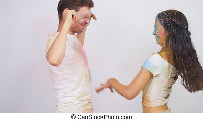 Young happy couple having fun playing with colorful holi...