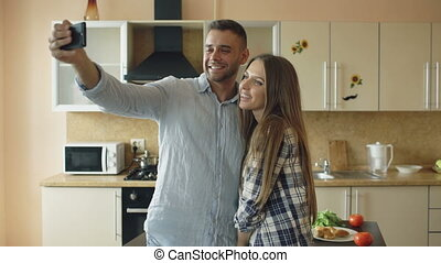 Young happy couple having online video chat in the kitchen at home