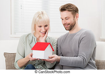 Couple Holding A House Model
