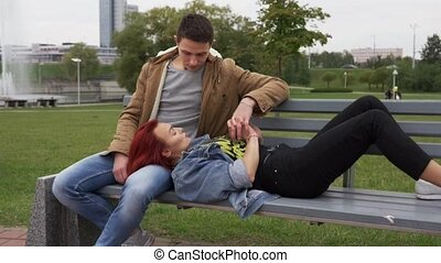 Young happy couple holding hands and resting together on bench in city park