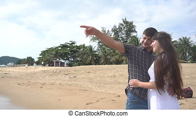 Young happy couple hug each other on the beach ang looking at the sea. Honeymoon, romance, just married.