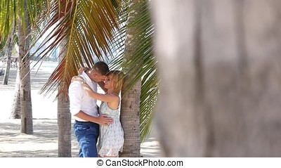Young happy couple hugging and kissing each other under a palm tree leaf. Romantic relationships or travel concept. HD, 1920x1080.