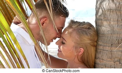 Young happy couple hugging and kissing each other under a palm tree leaf. Romantic relationships or travel concept.
