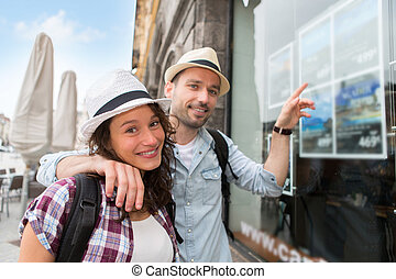 Young happy couple in front of travel agency - View of a...