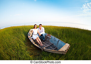 Young happy couple in love in a boat