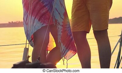 Young happy couple in love kissing on yacht and drink wine with glasses at amazing sunset in slowmotion.