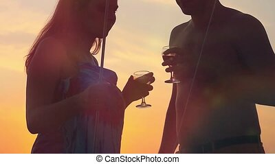 Young happy couple in love on yacht with glasses of wine at amazing sunset in slowmotion.