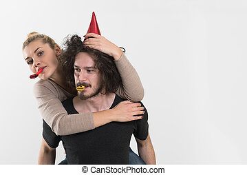 couple in party hats blowing in whistle