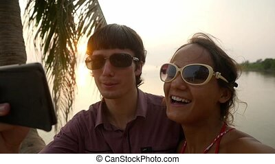 Young happy couple in sunglasses capturing romantic holidays...