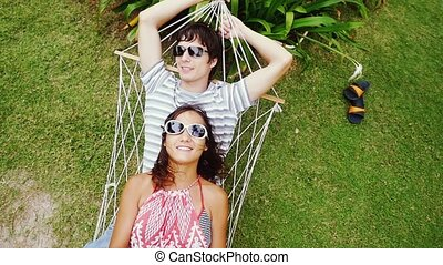 Young happy couple in sunglasses relaxing on hammock. Top of view. Slow motion.