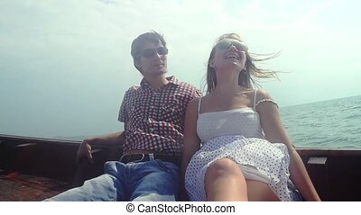 Young happy couple in sunglasses sit on drifting wooden boat enjoying their vacation. slow motion,