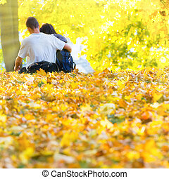 Young happy couple in the autumn park