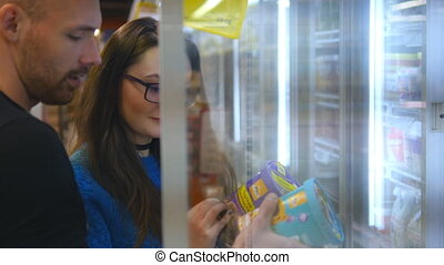 Young happy couple is standing by the freezer in grocery store and picking packages with frozen food. Pair taking product from the fridge and putting it into the basket. Choosing ice cream at store.