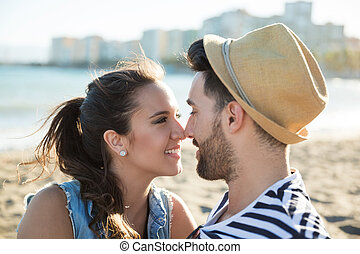 Young happy couple looking at each other on beach