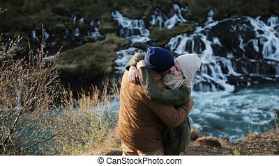 Young happy couple looking on Barnafoss waterfall in Iceland and jumping, raising hands . Man hugs and kisses woman