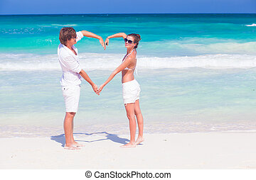 young happy couple making heart shape on tropical beach. honeymoon