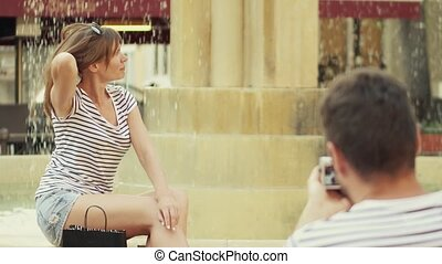 Young happy couple making photos near the fountain on their vacation
