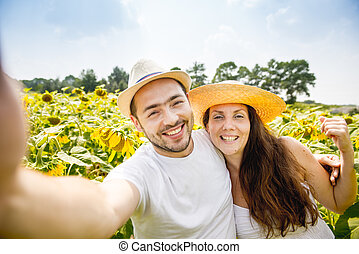 young happy couple man and woman are in a field of...