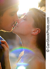 Young happy couple man and woman kissing light flare