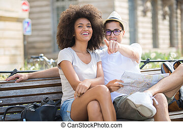 young happy couple on a bench at the park