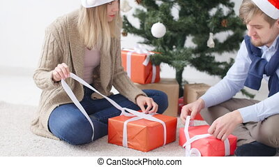 Young happy couple opens Christmas presents in a room with a white interior.