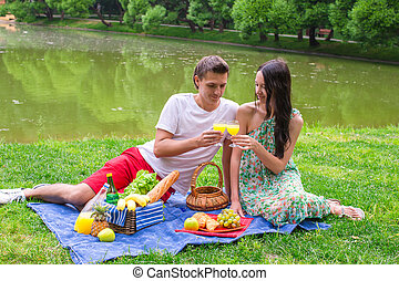 Young happy couple picnicking and relaxing outdoors