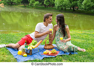 Young happy couple picnicking outdoors near the lake