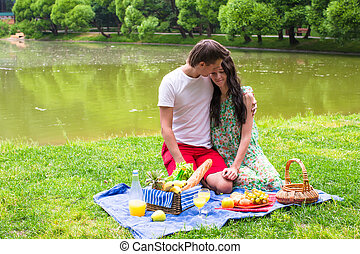 Young happy couple picnicking outdoors