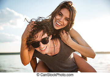 Young happy couple piggyback at the beach