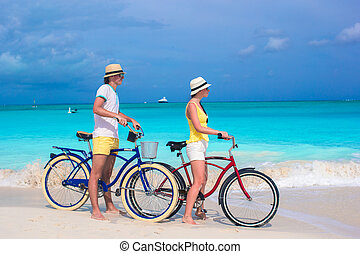 Young happy couple riding bikes on white tropical beach - ...