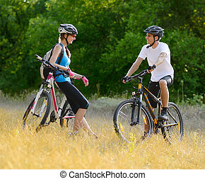 Young Happy Couple Riding Mountain Bikes Outdoor