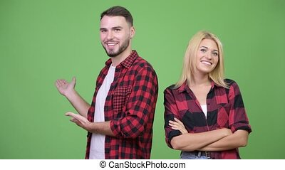 Young happy couple showing something together - Studio shot...