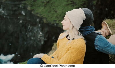 Young happy couple sitting at the edge of the cliff and resting. Tourist man and woman enjoying the beautiful landscape.