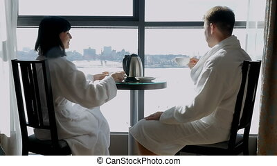 Young happy couple sitting by the window in hotel, at home. A woman and a man drink tea or coffee. A family