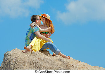 Young happy couple sitting in the mountains on a background of clouds