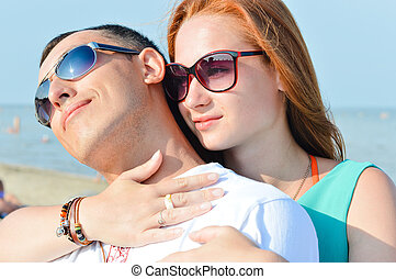 Young happy couple sitting on sandy beach and embracing wearing sun glasses