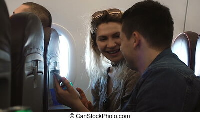 Young happy couple sitting on the plane near the window and...