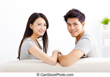 Young happy couple sitting on the sofa
