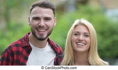 Young happy couple smiling together in the streets outdoors...