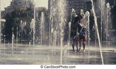 Young happy couple standing in the fountain