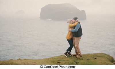 Young happy couple standing on the edge of the cliff and jumping of joy. Tourists man and woman hugging near the sea.