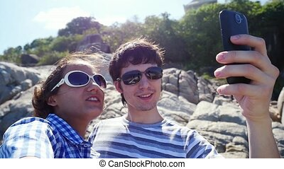 Young happy couple taking selfie by beautiful mountain with...
