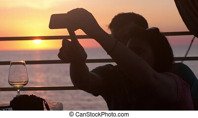 Young happy couple taking selfie photo with cellphone in beach cafe during beautiful sunset and drinking white wine. 3840x2160