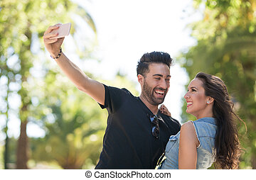 Young happy couple taking themselves photo laughing