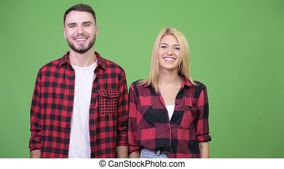 Young happy couple together against green background
