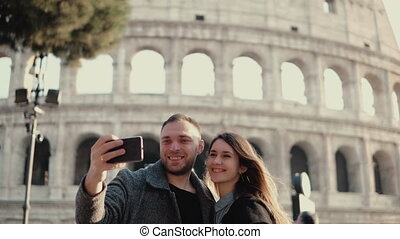 Young happy couple traveling in Rome, Italy. Man and woman taking the selfie photo on smartphone near the Colosseum.