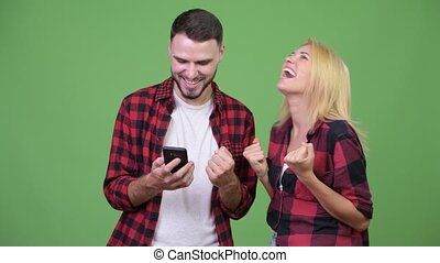 Young happy couple using phone together and getting good...